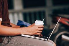 Το άτομο εργάζεται με τη χρησιμοποίηση ενός φορητού προσωπικού υπολογιστή στο εκλεκτής ποιότητας ξύλινο tabl στοκ φωτογραφία
