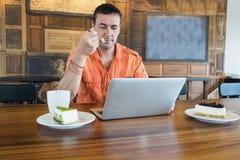 Το άτομο εργάζεται στον υπολογιστή και την πίτα, τρόφιμα στον υπολογιστή Στοκ Φωτογραφία