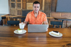 Το άτομο εργάζεται στον υπολογιστή και την πίτα, τρόφιμα στον υπολογιστή Στοκ Εικόνες