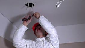 Το άτομο εργαζομένων αναρριχείται επάνω στη σκάλα και αφαιρεί τη μόνωση από τα καλώδια για το φωτισμό απόθεμα βίντεο