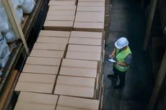 Το άτομο εργαζομένων αποθηκών εμπορευμάτων με το σκληρό καπέλο ασφάλειας ελέγχει τις λεπτομέρειες διαταγής με μια ψηφιακή ταμπλέτ στοκ εικόνα με δικαίωμα ελεύθερης χρήσης