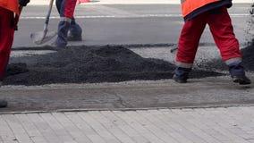 Το άτομο εργαζομένων βάζει την άσφαλτο σε μια οδική επίστρωση οδικής επισκευής Επισκευή των δρόμων Άσφαλτος απόθεμα βίντεο