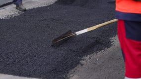 Το άτομο εργαζομένων βάζει την άσφαλτο σε μια οδική επίστρωση οδικής επισκευής Επισκευή των δρόμων Άσφαλτος φιλμ μικρού μήκους