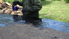 Το άτομο εργαζομένων βάζει την καυτή πίσσα με το εμπύρευμα καυστήρων αερίου στο κατώτατο σημείο βαρκών 4K απόθεμα βίντεο