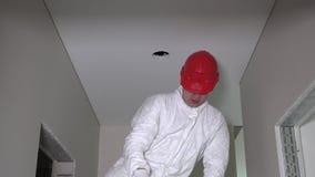 Το άτομο εργαζομένων κάνει τις ανώτατες τρύπες ξηρών τοίχων για την εγκατάσταση φωτισμού και αναρριχείται κάτω φιλμ μικρού μήκους