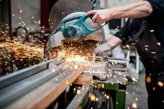 Το άτομο, εργαζόμενος που χρησιμοποιεί μια γλιστρώντας ένωση συνδέει λοξά το πριόνι στοκ φωτογραφία με δικαίωμα ελεύθερης χρήσης