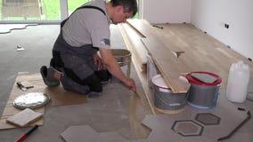 Το άτομο εφαρμόζει την κόλλα κόλλας στο πάτωμα για την τοποθέτηση πινάκων παρκέ απόθεμα βίντεο