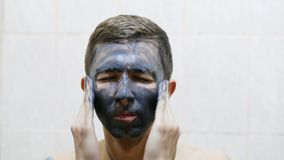 Το άτομο εφαρμόζει τη μαύρη μάσκα κρέμας στο πρόσωπο ενάντια στην ακμή απόθεμα βίντεο
