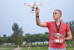 Το άτομο ελέγχει ένα quadrocopter στο πάρκο Στοκ Εικόνα