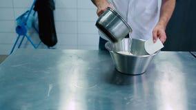 Το άτομο ζυμώνει τη ζύμη από το νερό και το αλεύρι φιλμ μικρού μήκους