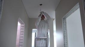 Το άτομο ηλεκτρολόγων με το κράνος αναρριχείται επάνω στη σκάλα και ξεβιδώνει τη λάμπα φωτός απόθεμα βίντεο
