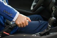 Το άτομο θέτει το αυτοκίνητο handbrake, που ανυψώνει το στην κορυφή στοκ φωτογραφία με δικαίωμα ελεύθερης χρήσης