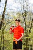 Το άτομο θέτει με μια ρακέτα αντισφαίρισης και ένα πορτοκαλί θερμοηλεκτρικό ζεύγος, στο υπόβαθρο του πράσινου πάρκου r στοκ εικόνες