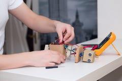 Το άτομο θέτει το τσιπ στο ρομπότ σε έναν άσπρο πίνακα ο βραχίονας απαρίθμησε τη βασική όψη της Στοκ εικόνα με δικαίωμα ελεύθερης χρήσης