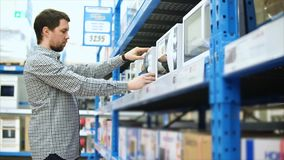 Το άτομο θέλει να αγοράσει ένα μικρόκυμα στο κατάστημα των οικιακών συσκευών απόθεμα βίντεο