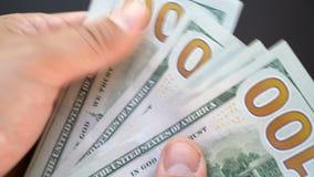 Το άτομο θεωρεί τα χρήματα με τα χέρια του μια κινηματογράφηση σε πρώτο πλάνο Δολάρια στην κινηματογράφηση σε πρώτο πλάνο βραχιόν απόθεμα βίντεο