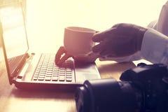 Το άτομο διαβάζει τις ειδήσεις στο lap-top και πίνει τον καυτό καφέ Στοκ Εικόνα