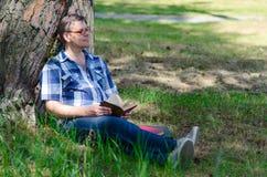 Το άτομο διαβάζει το βιβλίο στο δάσος πεύκων στοκ φωτογραφία με δικαίωμα ελεύθερης χρήσης