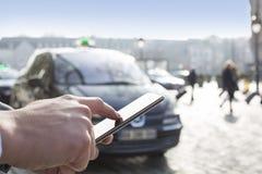 Το άτομο διατάζει ένα ταξί από το κινητό τηλέφωνό του Χέρια κινηματογραφήσεων σε πρώτο πλάνο Στοκ Φωτογραφίες