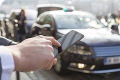 Το άτομο διατάζει ένα ταξί από το κινητό τηλέφωνό του Χέρια κινηματογραφήσεων σε πρώτο πλάνο Στοκ φωτογραφίες με δικαίωμα ελεύθερης χρήσης