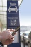 Το άτομο διατάζει ένα ταξί από το κινητό τηλέφωνό του Χέρια κινηματογραφήσεων σε πρώτο πλάνο Στοκ φωτογραφία με δικαίωμα ελεύθερης χρήσης