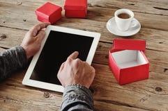 Το άτομο διατάζει τα δώρα Χριστουγέννων χρησιμοποιώντας έναν υπολογιστή ταμπλετών Στοκ φωτογραφία με δικαίωμα ελεύθερης χρήσης