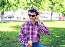 Το άτομο κάθεται, κρατώντας ένα έξυπνο τηλέφωνο, που μιλά στο τηλέφωνο, το καλοκαίρι στα γυαλιά και ένα πουκάμισο με ένα καπέλο Στοκ φωτογραφία με δικαίωμα ελεύθερης χρήσης