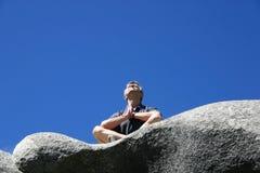 Το άτομο κάθεται σε έναν βράχο και προσεύχεται με τα υπόβαθρα του φωτεινού μπλε ουρανού Στοκ εικόνες με δικαίωμα ελεύθερης χρήσης