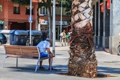 Το άτομο κάθεται σε έναν πάγκο και εξετάζει το τηλέφωνό του στοκ φωτογραφία