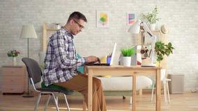 Το άτομο κάθεται σε ένα στρογγυλό ορθοπεδικό μαξιλάρι και αρχίζει σε ένα lap-top φιλμ μικρού μήκους