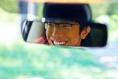 Το άτομο κάθεται στη θέση του οδηγού και κοιτάζει στον οπισθοσκόπο καθρέφτη Στοκ φωτογραφία με δικαίωμα ελεύθερης χρήσης