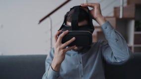 Το άτομο κάθεται στον καναπέ και προσπαθεί να κρατήσει και να χρησιμοποιήσει την ψηφιακή κάσκα τεχνολογίας καινοτομίας vr απόθεμα βίντεο