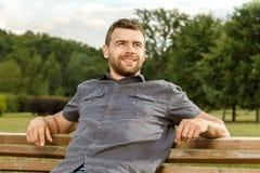 Το άτομο κάθεται στον πάγκο και χαλαρώνει στοκ εικόνα