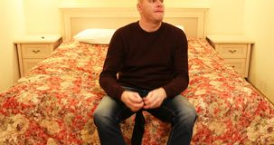 Το άτομο κάθεται στο κρεβάτι και βάζει τις μαύρες κάλτσες επάνω απόθεμα βίντεο
