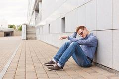 Το άτομο κάθεται την κλίση στον τοίχο και το έδαφος Στοκ εικόνες με δικαίωμα ελεύθερης χρήσης