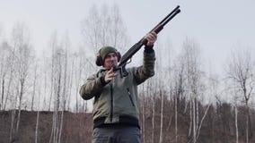 Το άτομο κάνει έναν πυροβολισμό από ένα κυνηγετικό όπλο και κάνει ένα θεαματικό ξαναφόρτωμα των όπλων με ένα χέρι απόθεμα βίντεο