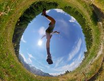 Το άτομο κάνει ένα άλμα σε ένα λιβάδι βουνών Όψη από κάτω από Φως της ημέρας Στοκ Φωτογραφίες