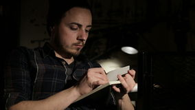 Το άτομο κάνει ένα σκίτσο σε ένα σημειωματάριο τη νύχτα σε έναν φραγμό απόθεμα βίντεο
