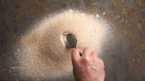 Το άτομο κάνει μια τρύπα με ένα κουτάλι σε έναν σωρό του αλευριού βίντεο φιλμ μικρού μήκους