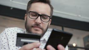 Το άτομο κάνει την πληρωμή on-line από την τηλεφωνική πίστωση τραπεζική κάρτα φιλμ μικρού μήκους