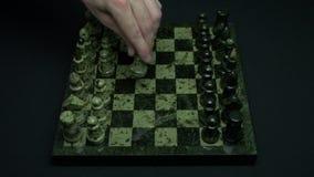 Το άτομο κάνει την πρώτη κίνηση σε ένα παιχνίδι σκακιού Αρχή του ανταγωνισμού Το πρώτο βήμα σκάκι χεριών και ένας πίνακας σκακιού απόθεμα βίντεο