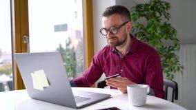 Το άτομο κάνει τη σε απευθείας σύνδεση πληρωμή στο σπίτι με μια πιστωτική κάρτα και ένα lap-top απόθεμα βίντεο
