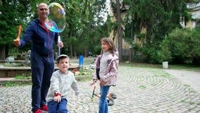 Το άτομο κάνει τις τεράστιες φυσαλίδες ουράνιων τόξων για τα παιδιά, τα ευτυχή παιδιά έχουν τη διασκέδαση με τις φυσαλίδες σαπουν απόθεμα βίντεο