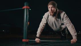 Το άτομο κάνει το ώθηση-UPS υπαίθρια στην αθλητική περιοχή στη νύχτα φιλμ μικρού μήκους