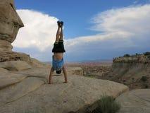 Το άτομο κάνει Handstand στους απότομους βράχους με το τοπίο τομέων στην έρημο Στοκ Εικόνα
