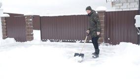Το άτομο καθαρίζει το δρόμο από το χιόνι φιλμ μικρού μήκους