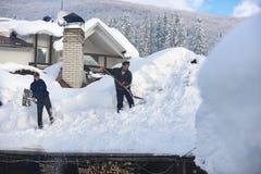 Το άτομο καθαρίζει τη στέγη του σπιτιού κατά τη διάρκεια χιονοπτώσεων το 2017 στοκ εικόνα