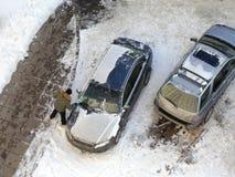 Το άτομο καθαρίζει τον ανεμοφράκτη από το χιόνι στοκ εικόνες με δικαίωμα ελεύθερης χρήσης