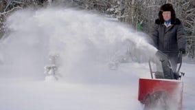Το άτομο καθαρίζει το χιόνι με το υπόβαθρο μηχανών αφαίρεσης χιονιού το δάσος το χειμώνα απόθεμα βίντεο