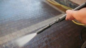 Το άτομο, καθαριστής, πλένει τους κυβόλινθους με αεροπλάνο του υψηλού νερού, κινηματογράφηση σε πρώτο πλάνο απόθεμα βίντεο